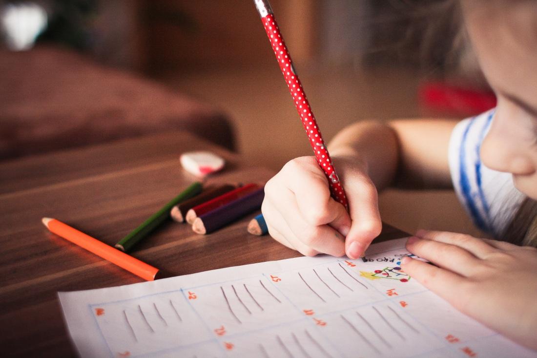 Chiild writing on worksheet
